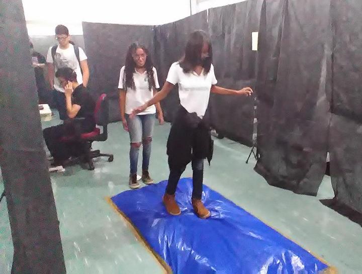 Aluna tenta caminhar por cima de chão que simula dificuldades encontrada por deficientes