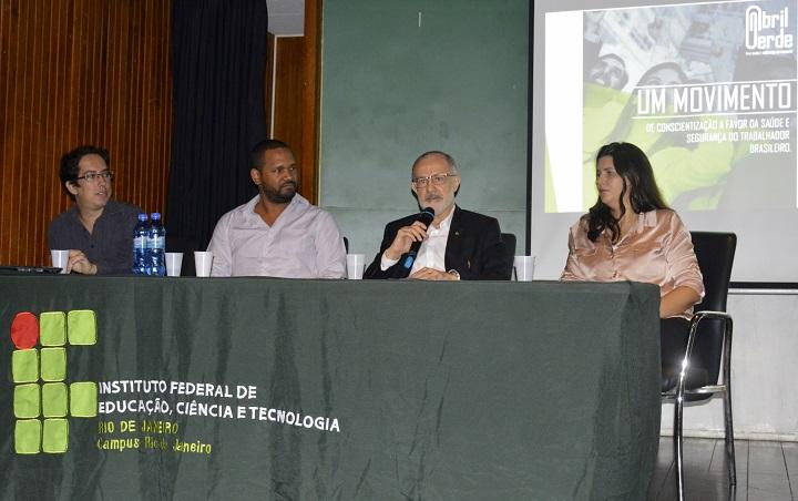 Quatro pessoas sentadas atrás da mesa com a logo do IFRJ. O reitor fala ao microfone.