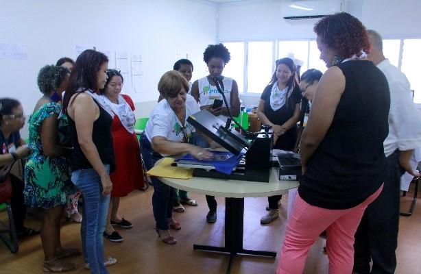 Mulher operando máquina de estampar camisetas, enquanto outras pessoas observam