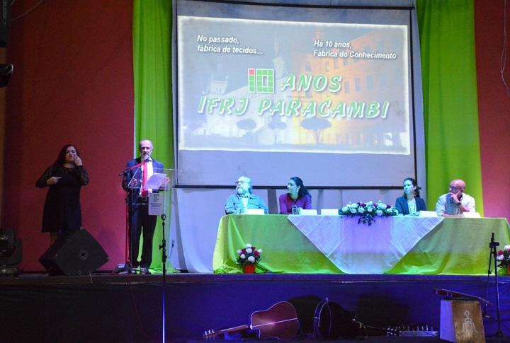 """Reitor fala ao microfone de pé ao lado da mesa de abertura e à frente de telão com dizeres """"10 anos IFRJ Paracambi"""""""