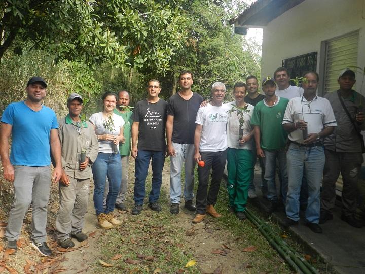Participantes do curso posam com mudas de plantas nas mãos