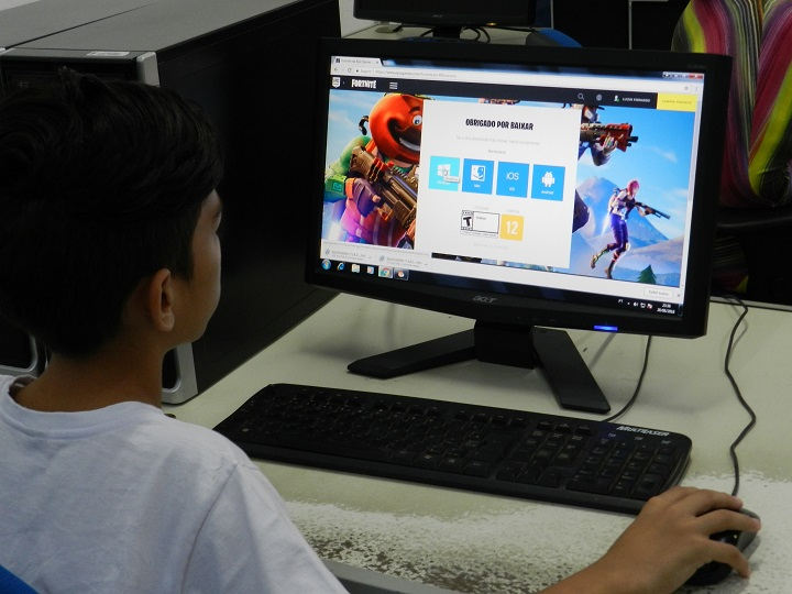 aluno mexendo no computador, tela aparecendo e aluno de costas