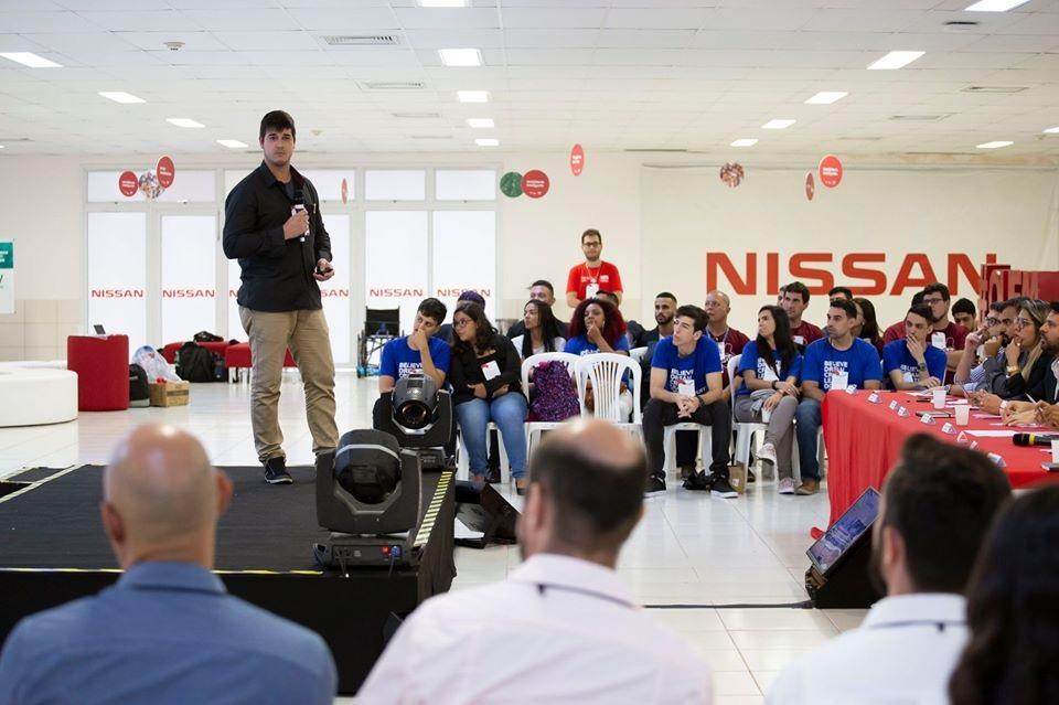 apresentação de aluno no palco da Nissan. ao fundo, participantes estão sentados, ao redor do palco