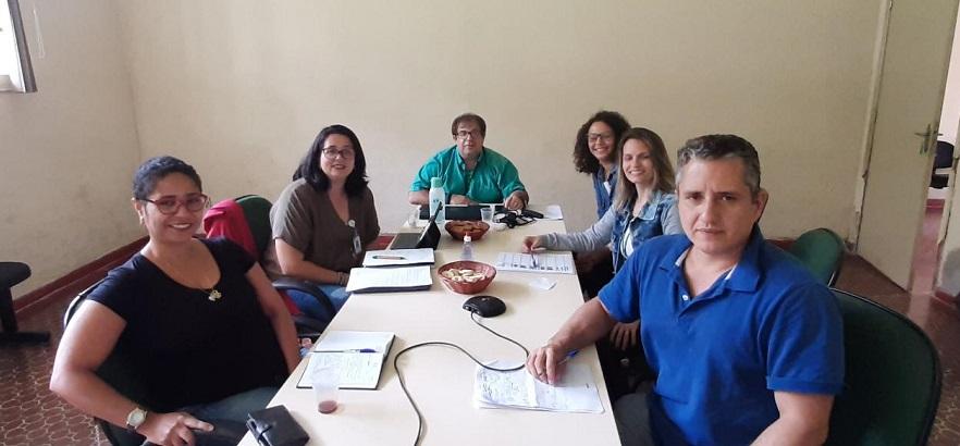 seis professores sentados ao redor de uma mesa, olhando para a camera