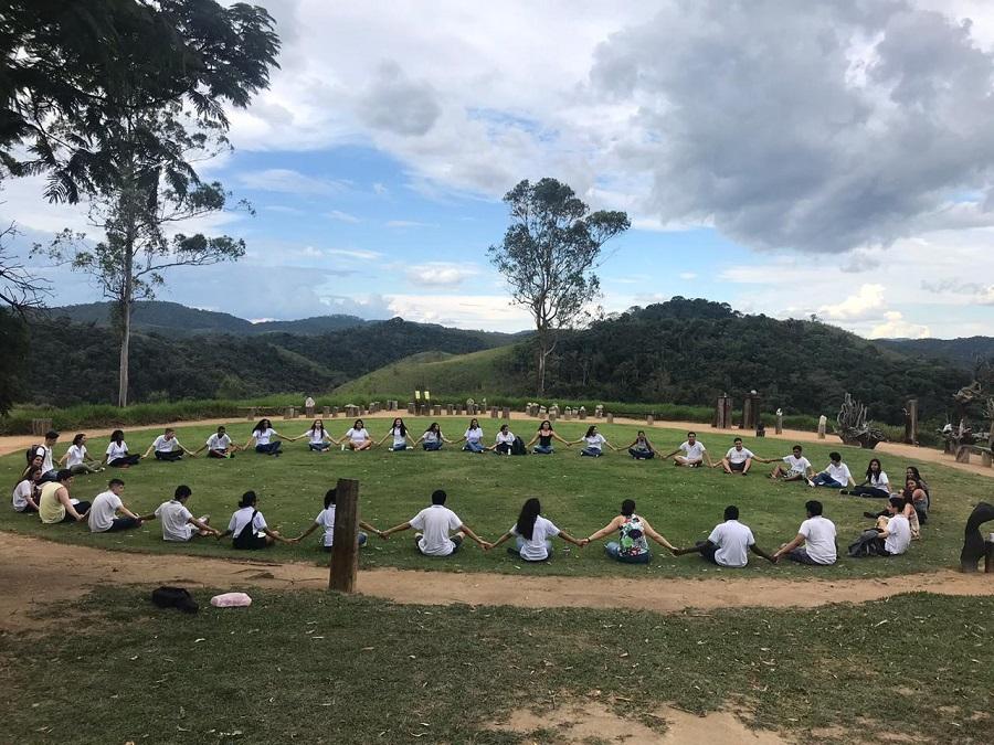 turma de alunos sentada em círuculo em um terreno aberto e gramado