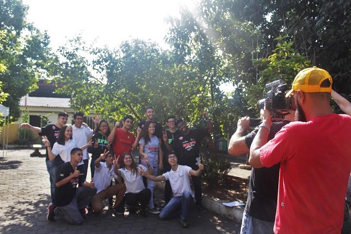 Câmera, em primeiro plano, filma grupo de alunos ao fundo