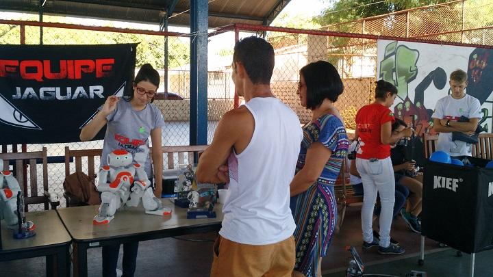 Pessoas observam aluna fazendo exposição de robôs numa mesa