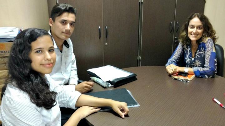 Marlon, sua assessora e Adriana Rigueira posam para a foto, sentados ao redor de uma mesa de reuniões