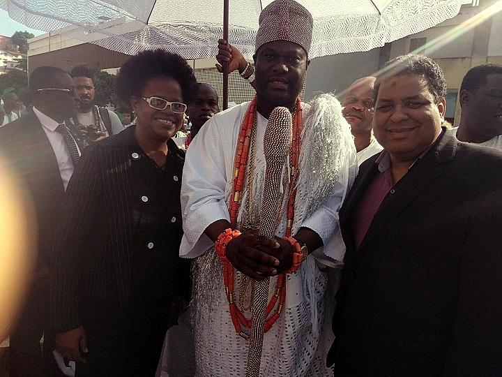 Uma professora, o rei (em trajes cerimoniais brancos e com o cajado) e o pró-reitor posam para a foto de pé