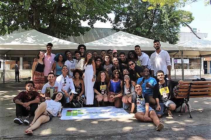 Alunos e professores reunidos, em volta de uma bandeira do IFRJ, na frente do local do evento
