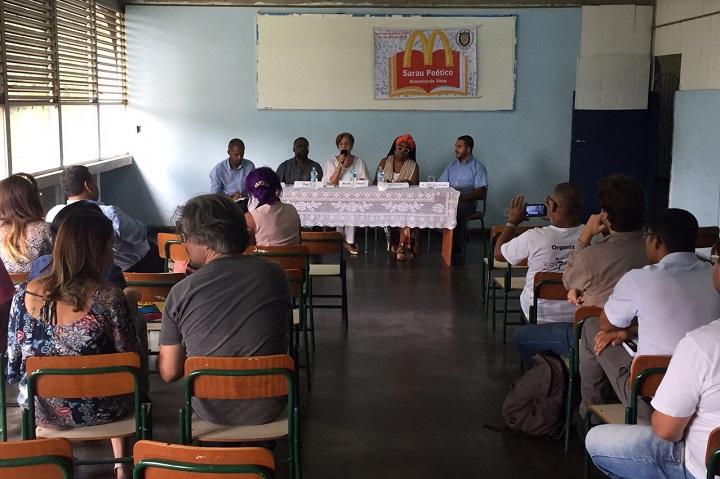 palestrantes sentados à mesa, na frente da sala, falam ao público