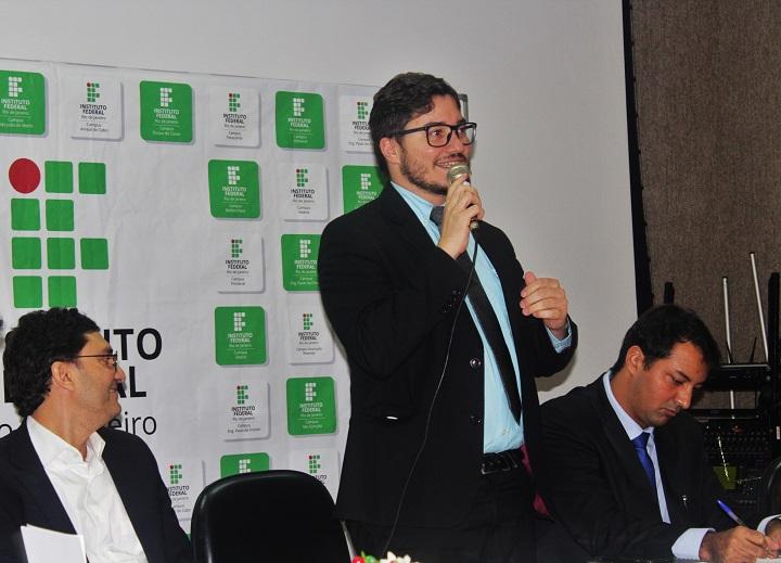 Reitor fala ao microfone de pé ao lado dos outros integrantes da mesa solene