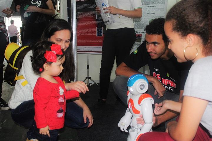 criança observando o robô NAO junto com alunos do campus volta redonda