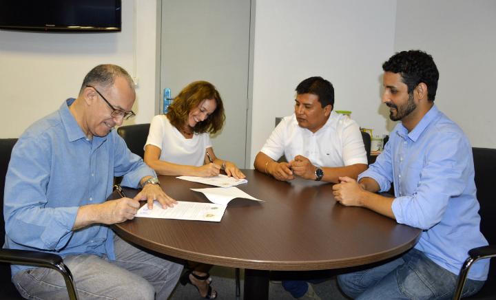 Reitor e assessora internacional do IFRJ assinam termo de parceria. Juntos, sentados ao redor da mesa, encontram-se também o representante do Peru e diretor de implantação do campus Belford Roxo.