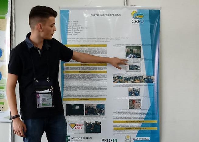 Aluno aponta foto em cartaz sobre projeto de Extensão
