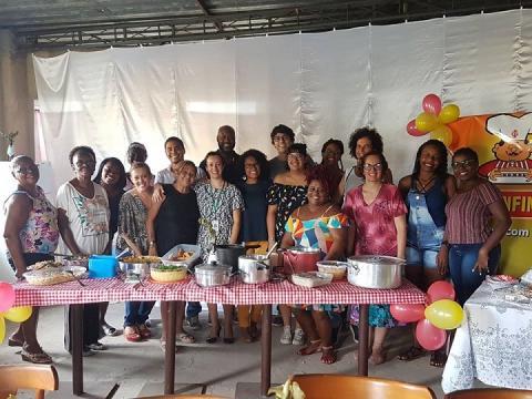 Alunos e professora posam para a foto atrás de mesa com pratos elaborados no curso