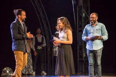 Alice recebendo placa do prêmio no palco, ladeada por dois dos organizadores