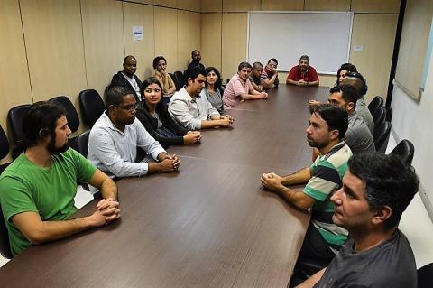 Servidores e pró-reitor ao redor de mesa de reuniões