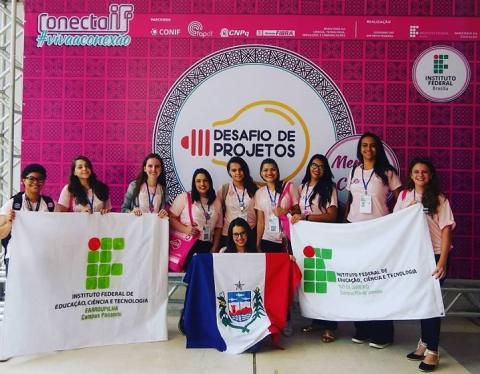Participantes do evento posam na frente de um banner rosa com logo do evento