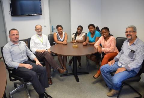 Reitor, profissionais do IFRJ e professoras moçambicanas posam para a foto sentados ao redor de uma mesa