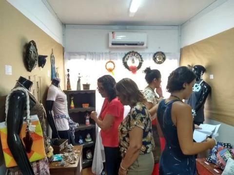 pessoas visitando a sala com exposição de peças artesanais