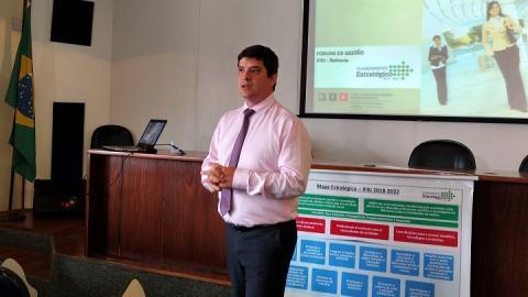Marcus Flávio Lenza fala à frente do auditório, com a projeção de slides ao fundo