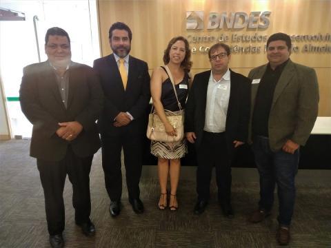Participantes da reunião em frente ao logo do BNDES