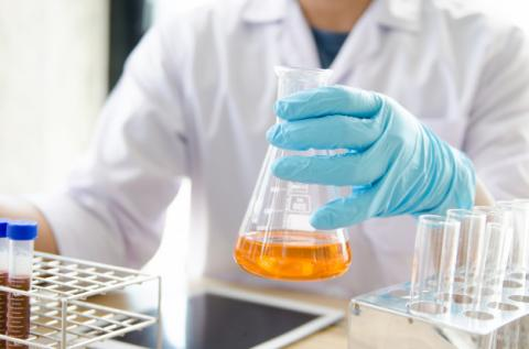 jovem cientista com luvas segurando um vidro com uma substância química dentro