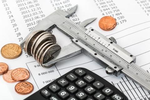 imagem mostra moedas, calculadora, um papel com uma lista de valores