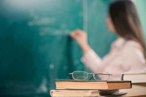 Professor escreve ao quadro ao fundo da imagem, com livros e óculos em primeiro plano