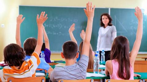 Professora na frente de um quadro negro olha para cinco crianças com as mãos levantadas
