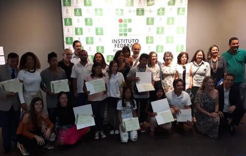 alunos concluintes posando com seus certificados para foto