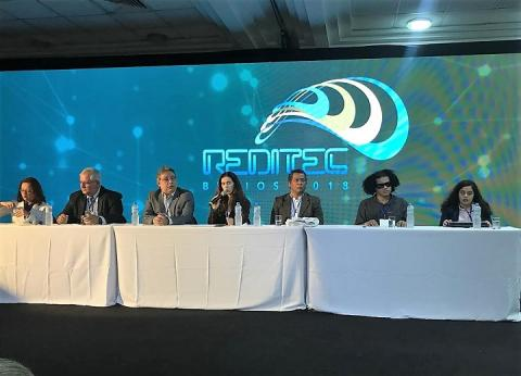 Integrantes da mesa-redonda sentados atrás da mesa na frente do auditório, com telão atrás com a logo da Reditec 2018
